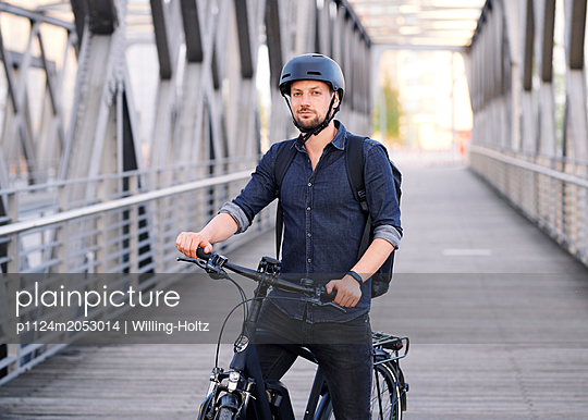 Bicycle courier riding an electric bike - p1124m2053014 by Willing-Holtz