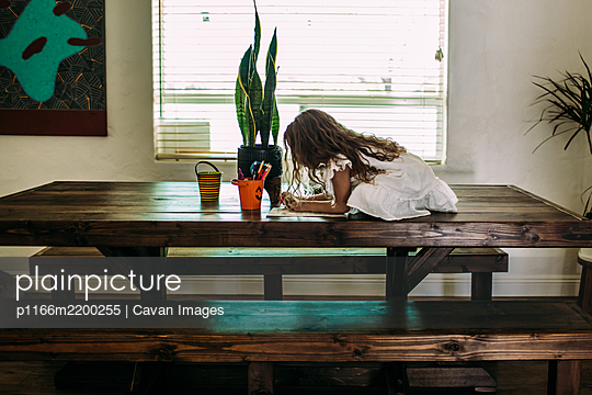young girl sitting on top of table coloring - p1166m2200255 by Cavan Images