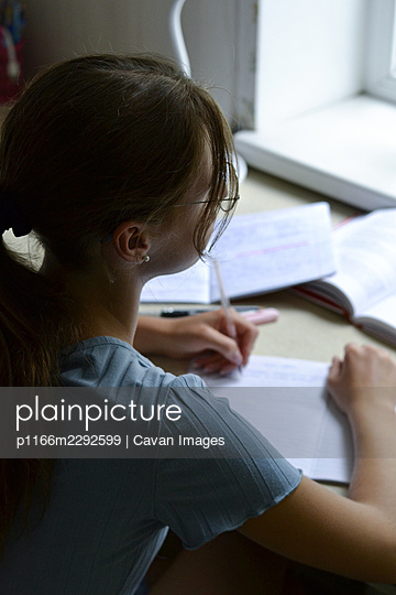 girl in glasses writing homework while sitting in her room - p1166m2292599 by Cavan Images
