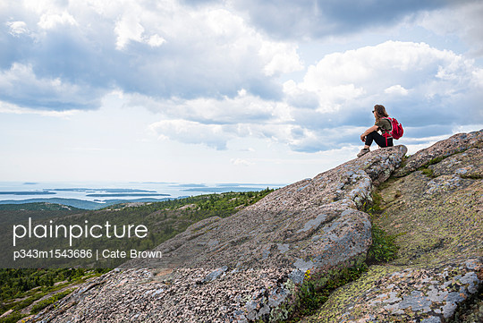 Female backpacker sitting and looking at view from summit of Cadillac Mountain in Acadia National Park, Bar Harbor, Maine, USA - p343m1543686 by Cate Brown
