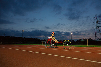 Portrait confident teenage girl paraplegic athlete training for wheelchair race on sports track at night - p1023m2067577 by Martin Barraud