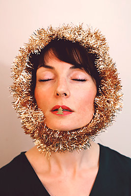 Woman with Christmas wreath around the head and little golden Christmas tree on the lips - p1521m2141348 by Charlotte Zobel