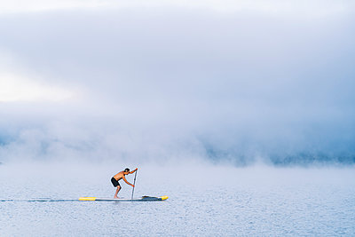 Man stand up paddle surfing on a lake in the fog - p300m2169974 by Daniel González