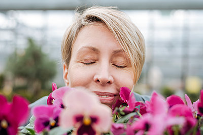 Smiling woman smelling on pansies in flower shop - p300m2171369 by Katharina und Ekaterina