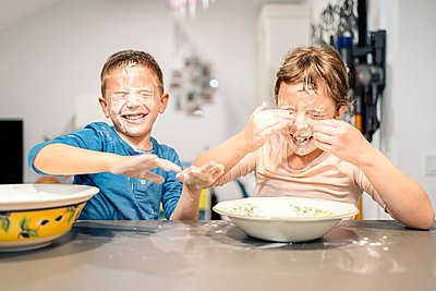 Happy siblings playing with flour and water at home - p300m2273606 by Albert Martínez