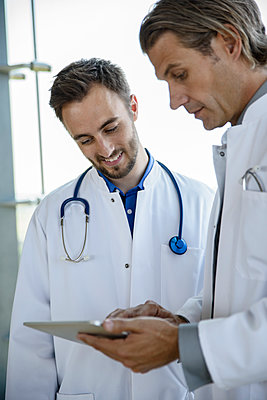 Mid adult male doctor discussing treatment with coworker over digital tablet at hospital - p300m2273791 by Buero Monaco