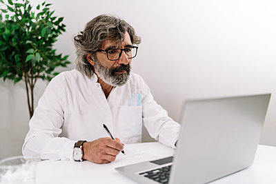 Serious businessman writing on paper while working on laptop at office - p300m2275268 by COROIMAGE