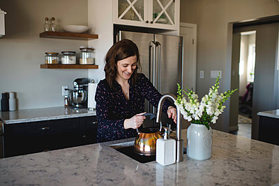Woman filling up kettle at kitchen sink - p429m1418419 by Erin Lester