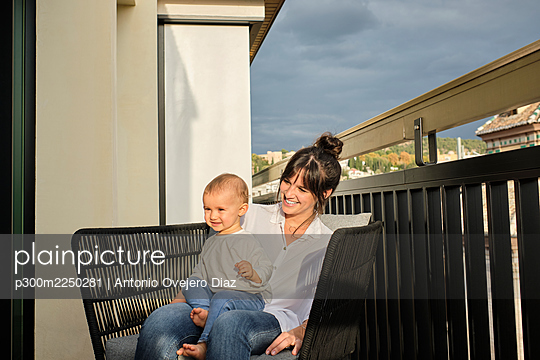 Mother and baby daughter sitting together in armchair on balcony - p300m2250281 by Antonio Ovejero Diaz