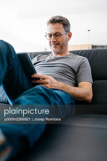 Smiling mature man using digital tablet while sitting on sofa - p300m2266921 by Josep Rovirosa