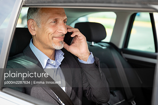 Portrait from car window of senior business man sitting in the back talking on mobile phone; Florence, Italy - p300m2287634 von Emma Innocenti