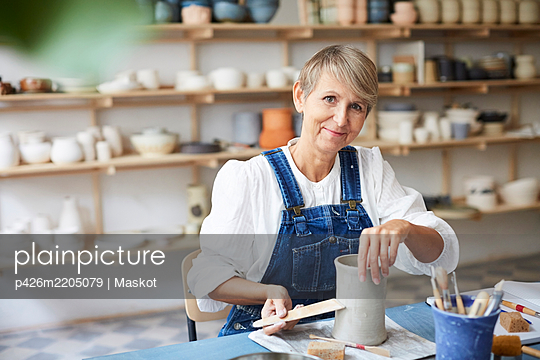 Portrait of smiling mature woman with earthenware at table in art studio - p426m2205079 by Maskot