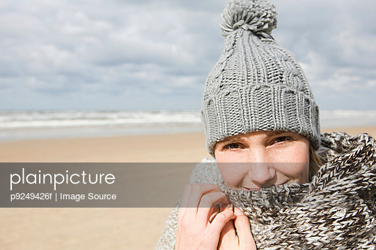 Woman in hat and scarf by the sea - p9249426f by Image Source