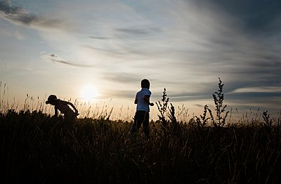 silhouette of brother and sister playing in a meadow at sunset - p1166m2137845 by Cavan Images