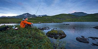 Norway, Troms, Sjuendevatnet, Man fishing in lake at dusk - p352m1349421 by Gustaf Emanuelsson