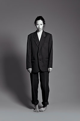Barefoot Asian woman wearing large suit - p555m1303676 by Sophie Filippova