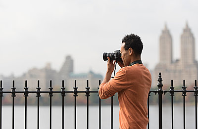 Mixed race man taking photograph on urban waterfront - p555m1414388 by JGI/Tom Grill