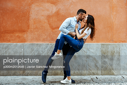 Affectionate couple in love kissing in front of a wall outdoors - p300m2012646 von Javier Sánchez Mingorance