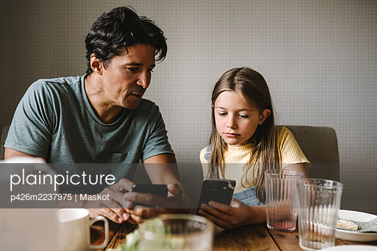 Daughter and father using smart phone over dining table at home - p426m2237975 by Maskot