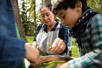 Grandmother and grandsons shelling peas - p1192m2109652 by Hero Images