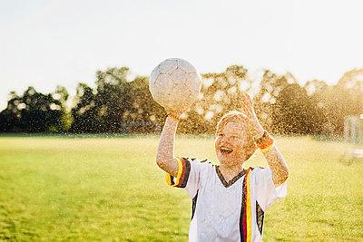 Boy wearing German soccer shirt screaming for joy, standing in water splashes - p300m2004673 by Jana Mänz