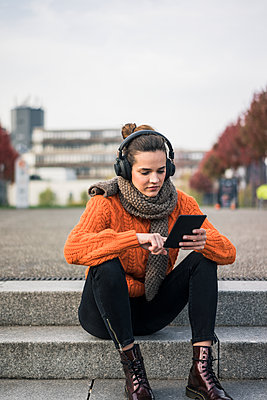 Portrait of fashionable woman sitting on steps outdoors using tablet and cordless headphones - p300m2069797 von Robijn Page