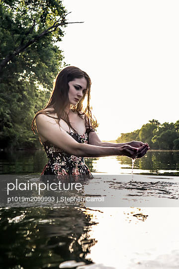 Woman refreshes herself in the river - p1019m2099993 by Stephen Carroll