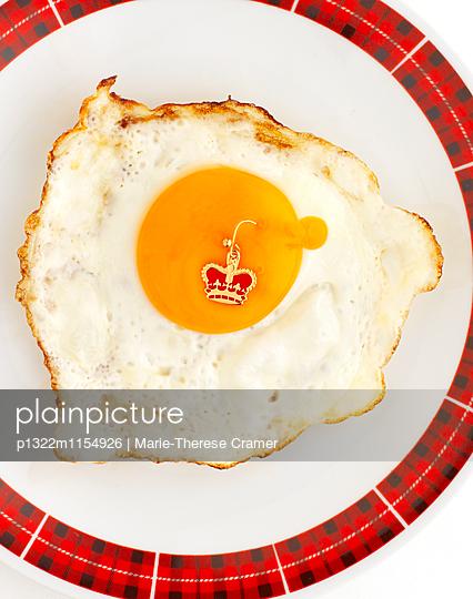 Spiegelei auf einem Teller mit einem Ohrring ins Dotter gepiekst - p1322m1154926 von Marie-Therese Cramer