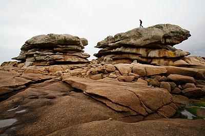 Man on rocks, Tregastel, Brittany Coast, France - p1028m2179264 by Jean Marmeisse