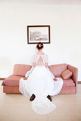 Bride and groom on sofa - p1105m2126387 by Virginie Plauchut