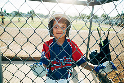 Portrait of happy baseball player standing behind chainlink fence - p1166m1474317 by Cavan Images