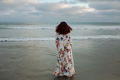 Rear view of woman standing on shore at beach against cloudy sky - p1166m1509167 by Cavan Images