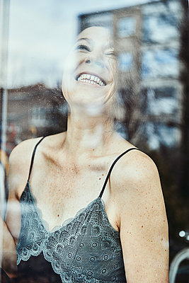 sixty year old woman smiling at a window - p1540m2152716 by Marie Tercafs