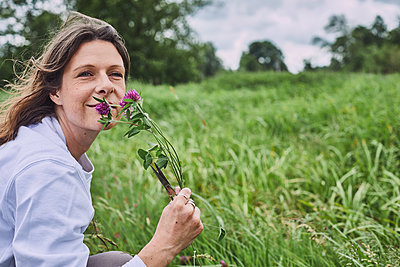 Woman smelling red clover on a meadow - p1573m2289123 by Christian Bendel