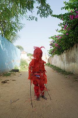 African boy in red disguise - p1610m2181464 by myriam tirler