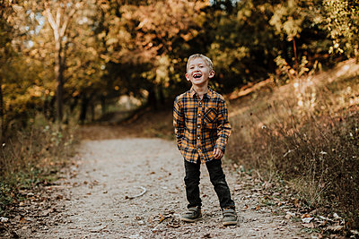 Cheerful boy looking away while standing on forest path - p300m2240613 by Gala Martínez López