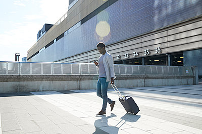 Male entrepreneur pulling luggage while using mobile phone against station in city - p300m2241537 von Pete Muller