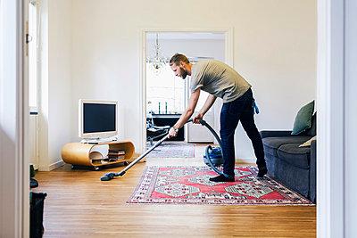 Side view of man vacuuming hardwood floor - p426m1017961f by Maskot