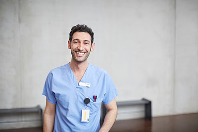 Portrait of smiling young male nurse in blue scrubs standing against wall at hospital - p426m2018930 by Maskot