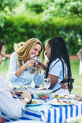 Happy female friends toasting wineglasses at dining table during garden party - p426m2135610 by Maskot