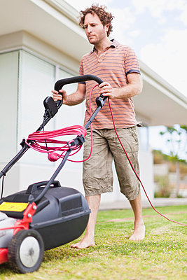 Man mowing green lawn - p429m800883f by Hybrid Images