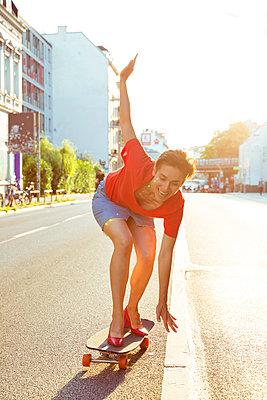 Frau fährt Skateboard auf der Straße - p432m1468025 von mia takahara