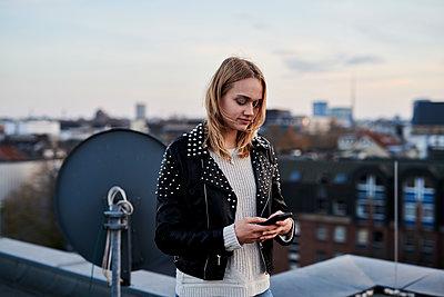 Junge Frau schreibt eine SMS auf einem Hausdach - p890m2231033 von Mielek