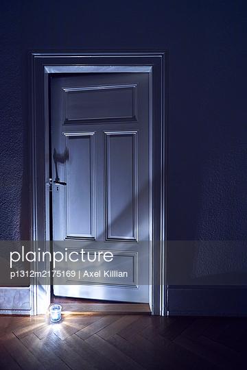 Zimmertür einer Altbauwohnung mit Teelicht am Fußboden - p1312m2175169 von Axel Killian