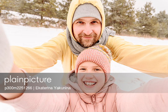 Close-up portrait of smiling father and daughter on snowy landscape - p300m2251266 by Ekaterina Yakunina