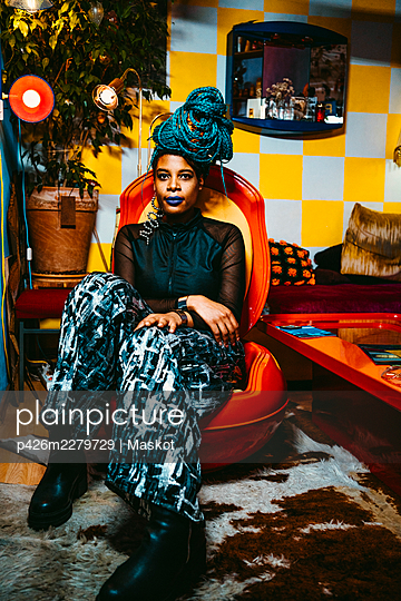 Full length of mid adult woman sitting on chair in living room - p426m2279729 by Maskot