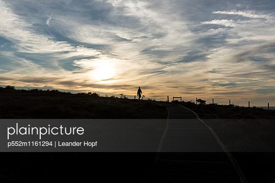 Mann macht einen Spaziergang bei Sonnenuntergang - p552m1161294 von Leander Hopf