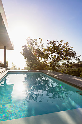Tranquil sunny reflection of tree over lap swimming pool on luxury patio - p1023m1443276 by Martin Barraud
