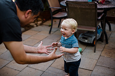 Uncle Playing with Nephew in Yard in San Diego - p1166m2216881 by Cavan Images