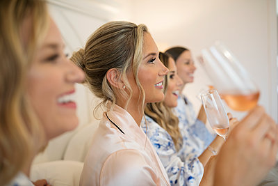 Smiling bride and bridesmaids drinking champagne at wedding - p1192m1529790 by Hero Images